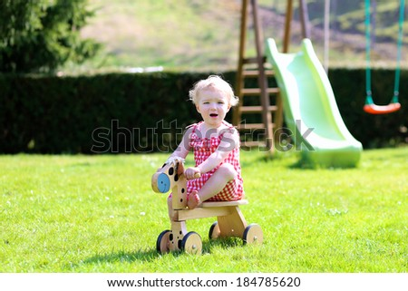 Happy little kid, cute blonde toddler girl playing outdoors in the garden at the backyard of the house riding on green lawn with wooden horse on a sunny summer day - stock photo