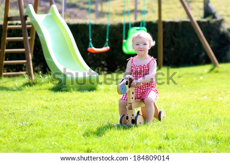 Happy little kid, cute blonde toddler girl playing outdoors in the garden at the backyard of the house riding on green lawn with wooden horse on a sunny summer day