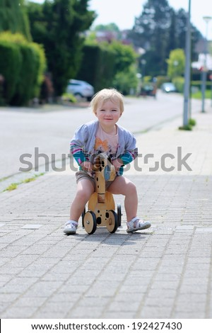 Happy little kid, cute blonde toddler girl playing outdoors on the street riding her push bike, wooden horse with wheels, on a sunny summer day - stock photo