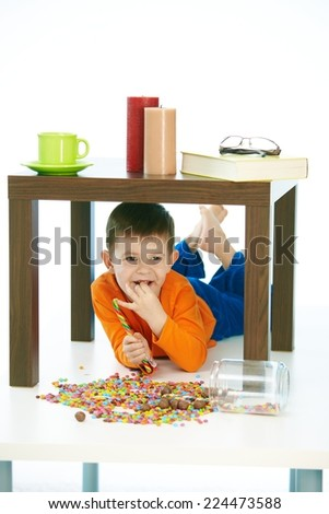 Happy little kid eating sweets under table at home. Lying on belly, happy, smiling, isolated on white - stock photo