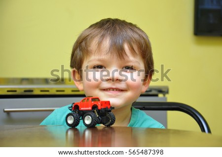 Happy little kid play with his monster truck. Excited boy looks at his new toy car