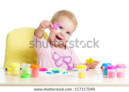 Happy little kid sitting at table and playing with colorful clay toy - stock photo