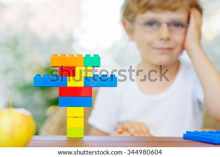 Happy little kid with glasses playing with lots of colorful plastic blocks indoor. child boy having fun with building and creating. Selective focus on multicolored toy - stock photo