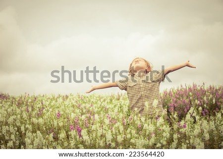 Happy little kid with raised up arms in green  field of flowers. Concept of freedom and happiness - stock photo