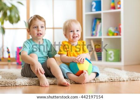 Happy little kids boys friends sitting on floor in kindergarten - stock photo