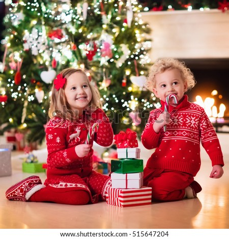 Happy little kids in matching red knitted sweaters decorate Christmas tree in beautiful living room with traditional fire place. Children opening presents on Xmas eve.