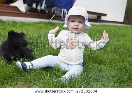 Happy little one year girl having fun at grass with dog - stock photo