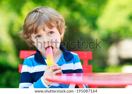 Happy little preschool boy eating colorful ice cream in summer, outdoors. - stock photo