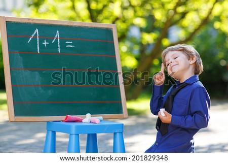 Happy little preschooler at blackboard practicing mathematics, outdoors. Back to school concept. - stock photo
