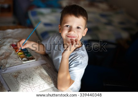 Happy little preschooler boy painting coloring book at home