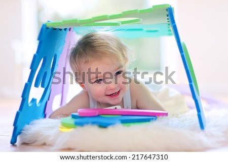 Happy little preschooler child, adorable toddler girl playing hide and seek and learning numbers with colorful soft puzzles - stock photo