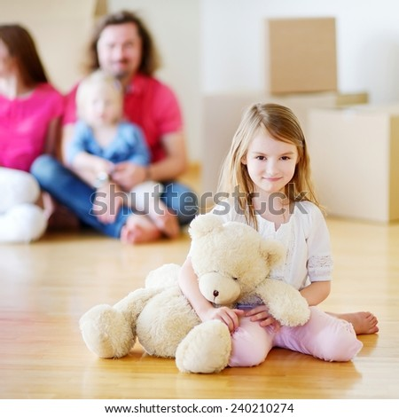 Happy little preschooler girl with a toy moving in her new home with parents and a sister - stock photo