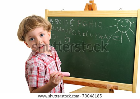 Happy little school boy writing on the blackboard - stock photo