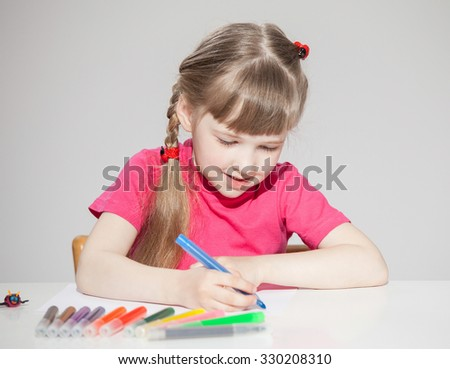 Happy little school girl drawing, neutral background - stock photo