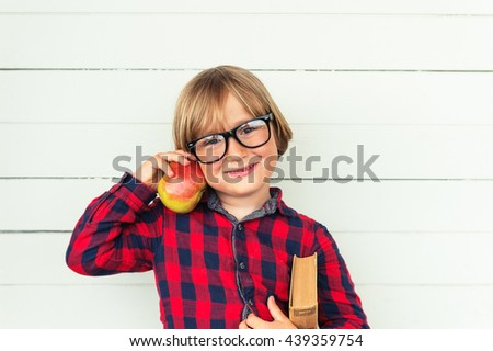 Happy little schoolboy holding book and red apple, wearing white red and blue plaid shirt and black frame eyeglasses, standing against white wooden background. Back to school concept - stock photo