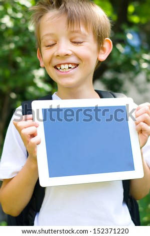 Happy little schoolboy with backpack and  tablet computer outdoors - stock photo