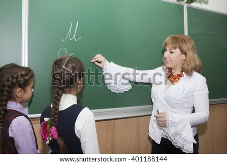 Happy little schoolgirl and teacher at the blackboard