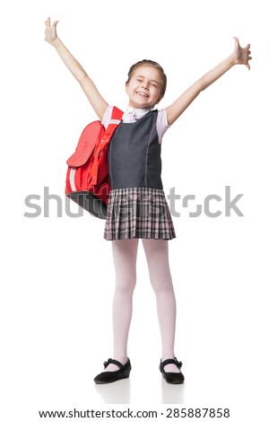 Happy little schoolgirl in uniform standing on white background  - stock photo