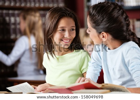 Happy little schoolgirl looking at female friend while studying in library - stock photo