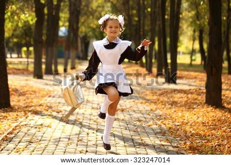 Happy little schoolgirl run home from school, outdoor autumn park - stock photo