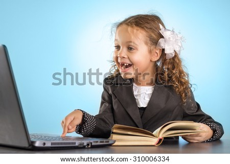 Happy Little Schoolgirl Sits At Table With Book Shows A Finger Into The Laptop On Blue Background - stock photo