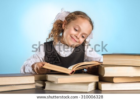 Happy Little Schoolgirl Sits At Table With Books On Blue Background - stock photo