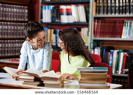 Happy little schoolgirls looking at each other while studying at table in library - stock photo