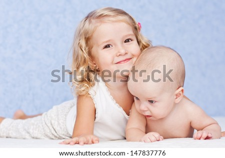 happy little sister hugging her brother lying