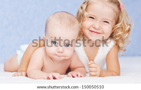 happy little sister hugging her brother lying  - stock photo