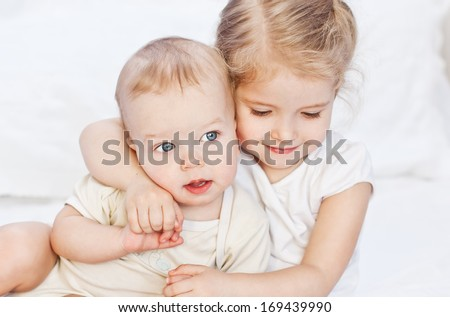 happy little sister hugging her brother on a white background - stock photo