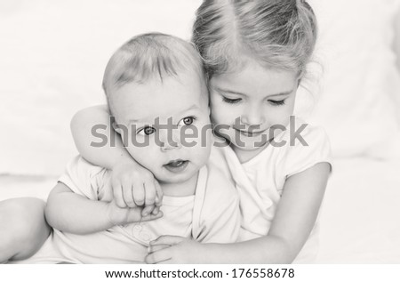 happy little sister hugging her brother on a white background ( black-white ) - stock photo