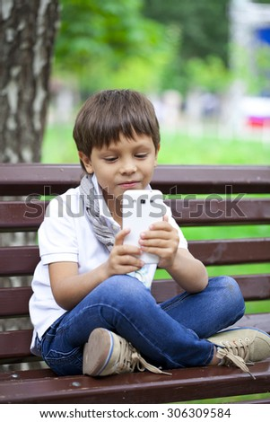 Happy Little smiling child boy hand holding mobile phone or smartphone making selfie portrait photoon a background of summer park - stock photo