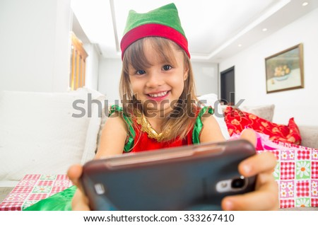 Happy little smiling girl dressed in Christmas dress holding mobile phone - stock photo