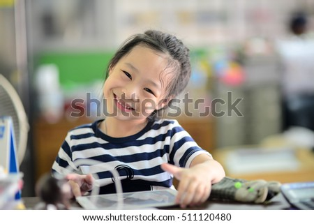 Happy little student Asian girl with tablet pc at home