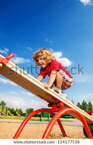 Happy little three years old boy child walking over seesaw keeping balance - stock photo