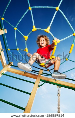 Happy little three years old child boy climbed on top of the rope web on playground looking down and laughing