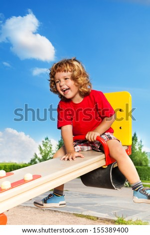 Happy little three years old child boy sitting and laughing on the seesaw - stock photo