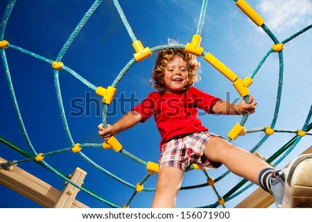 Happy little three years old child boy sitting on the web on playground and smiling ready to jump - stock photo