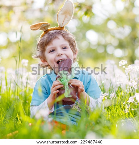 Happy little toddler boy eating chocolate and wearing Easter bunny ears, sitting in blooming garden on warm sunny day. Celebrating Easter traditional holiday. - stock photo