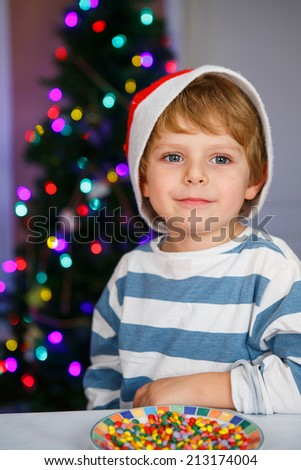 Happy little toddler boy in santa hat with christmas tree and lights on background eating sweets - stock photo