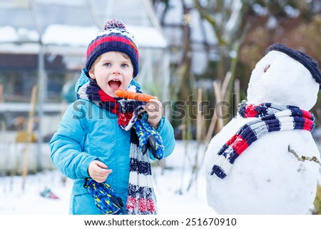 Happy little toddler boy making a snowman and eating carrot, playing and having fun with snow, outdoors  on cold day. Active outoors leisure with kids in winter. - stock photo