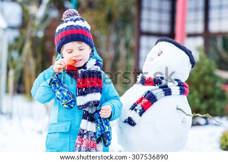 Happy little toddler boy making a snowman and eating carrot, playing and having fun with snow, outdoors  on cold day. Active outside leisure with kids in winter. - stock photo