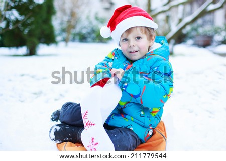 Happy little toddler boy with present waiting for Christmas santa hat, sitting on snow in winter garden, outdoors.