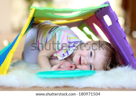 Happy little toddler girl playing hide and seek and learning numbers with colorful soft puzzles - stock photo