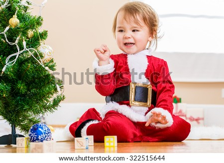 Happy little toddler girl playing near the Christmas tree - stock photo