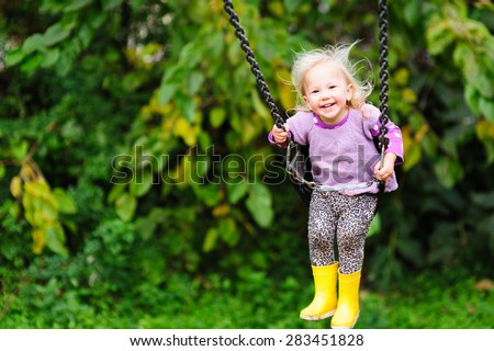 Happy little toddler girl wearing gumboots and warm vest having fun on a swing in the park on a chilly autumn or summer day
