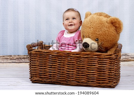 Happy little toddler in the basket with teddy bear