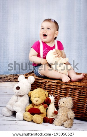 Happy little toddler with plush toys
