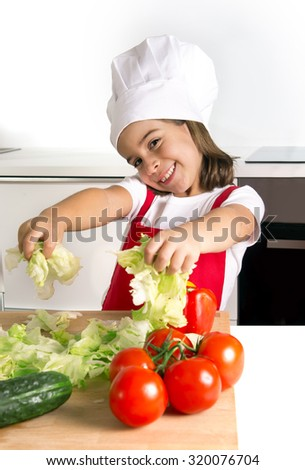 happy little 4 years old girl playing with vegetables at home kitchen wearing apron and cook hat having fun grabbing lettuce in healthy nutrition and education concept - stock photo