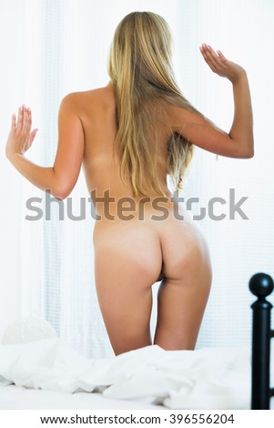 Happy long-haired blonde young girl posing in bedroom naked - stock photo